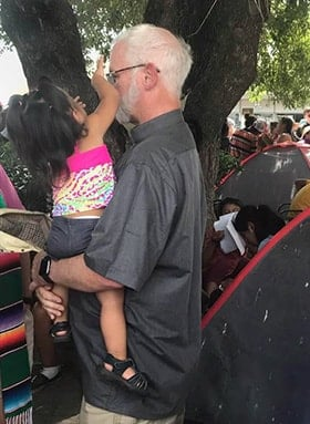 The Rev. Larry Duggins, a United Methodist elder and executive director of the Missional Wisdom Foundation, holds a child from Honduras during a visit to Matamoros, Mexico. Duggins was part of an ecumenical group that went to the border out of concern about a U.S. policy requiring some asylum seekers to remain in Mexico as their cases are considered. Photo Courtesy of Texas Impact.