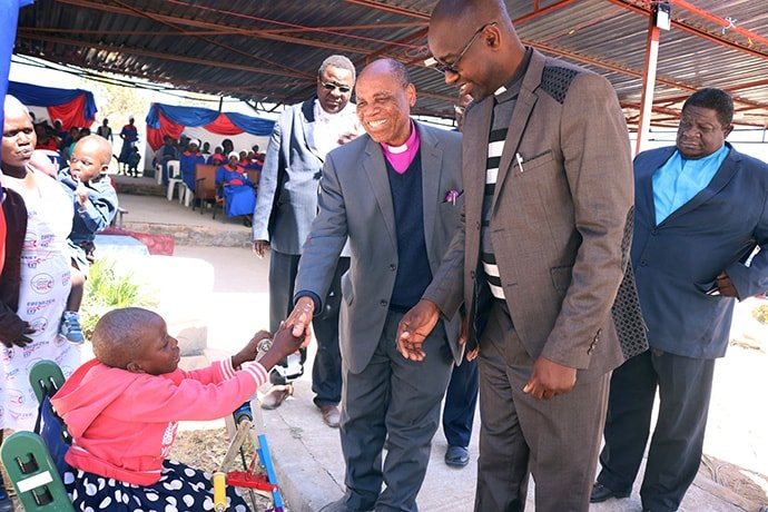 """Portia Kasuso shakes hands with Bishop Eben K. Nhiwatiwa during a United Methodist revival service in Murewa. The young girl was a guest of honor at the service. """"Having Portia at this revival is evidence of how much the church can become a home for all people in spite of their conditions,"""" Nhiwatiwa said. Photo by the Rev. Taurai Emmanuel Maforo, UM News."""