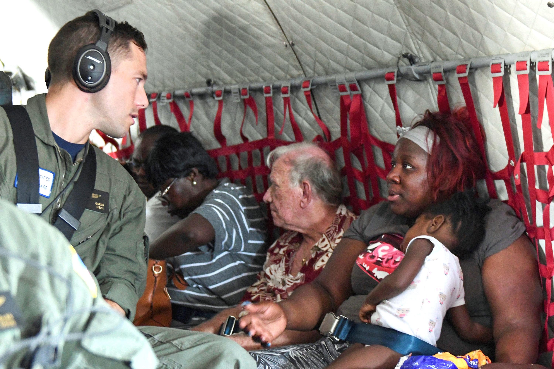 9월 5일, 해안 경비대원이 HC-144대양경비 항공기에 탑승한 민간인과 대화하고 있다.  마이애미에 기지를 둔 이 헬기 수송기는 허리케인 도리언으로 피해를 당한 열 명의 주민을 마쉬 하버에서 바하마의 낫소로 이동시켰다. 사진 제공 미 국방부.