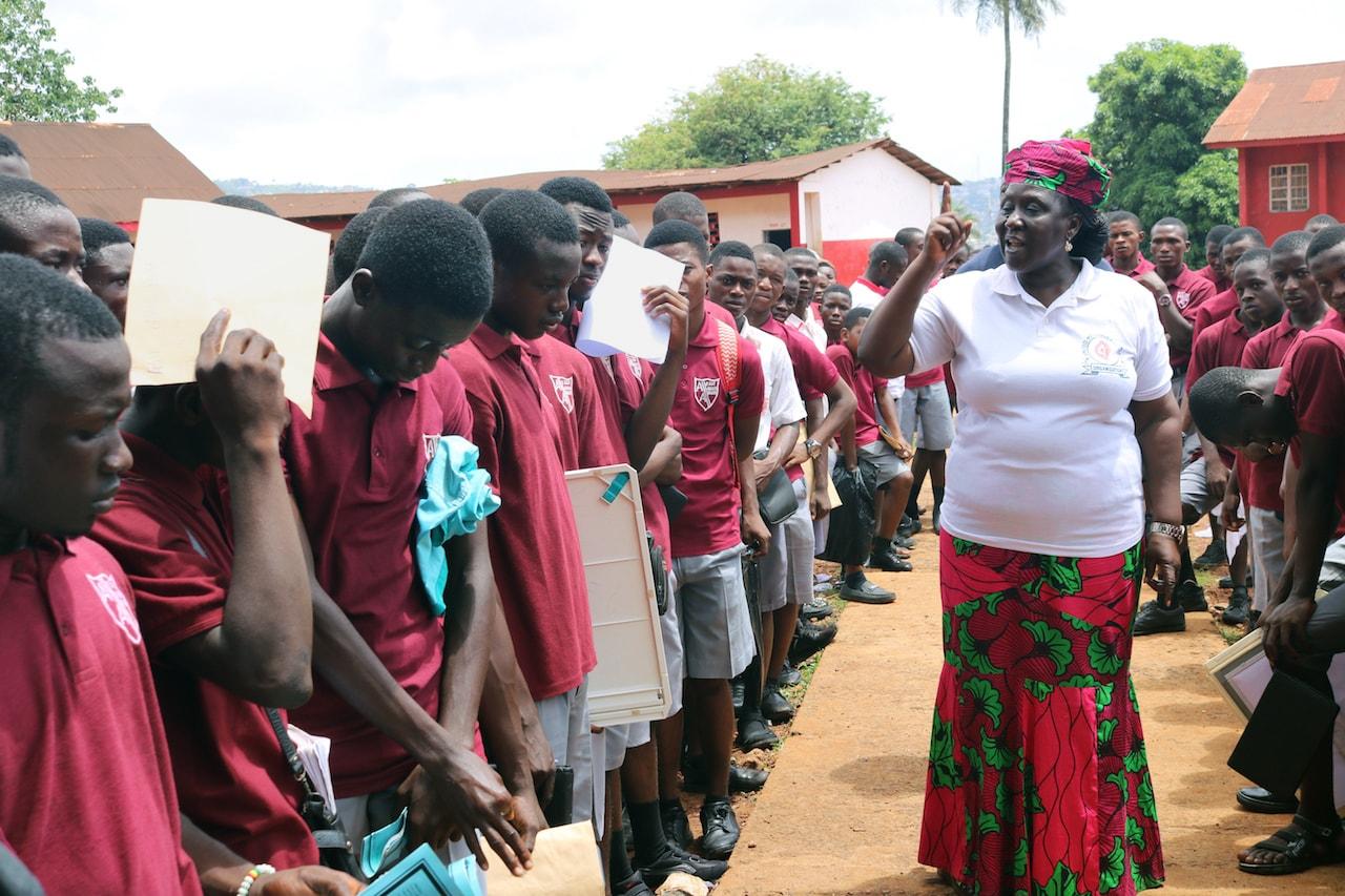 Ethel Sandy, coordinadora de Mujeres Metodistas Unidas, habla con los estudiantes de la Academia Albert, la única escuela secundaria de niños metodistas unidos en Freetown, Sierra Leona, sobre los peligros de hacer trampa en los exámenes. Foto por Phileas Jusu, Noticias MU.