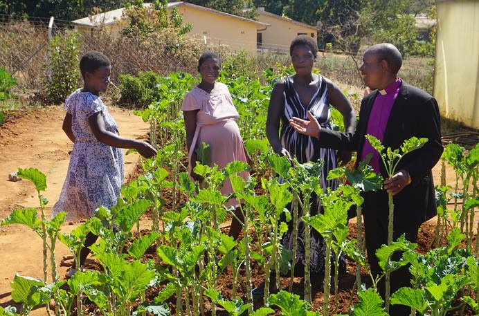 Expectant mothers give Bishop Eben K. Nhiwatiwa a tour of the vegetable garden they are tending at the Old Mutare Mission Hospital in Mutare, Zimbabwe. The garden provides nutrition, exercise and an opportunity to learn skills they can use when they return home after delivering their babies. From left are: Resistance Maphosa, Marvellous Chimbidzikai and Sophia Chindondondo. Photo by Kudzai Chingwe, UM News.