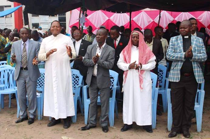 An ecumenical group that includes United Methodists, Roman Catholics, Muslims and other revival churches gather in Lodja, Congo, for a prayer gathering for a peaceful election process in the Sankuru Province. In the black pastoral dress is the Rev. Robert Shuyaka, a United Methodist pastor. Photo by Francois Omanyondo, UM News.