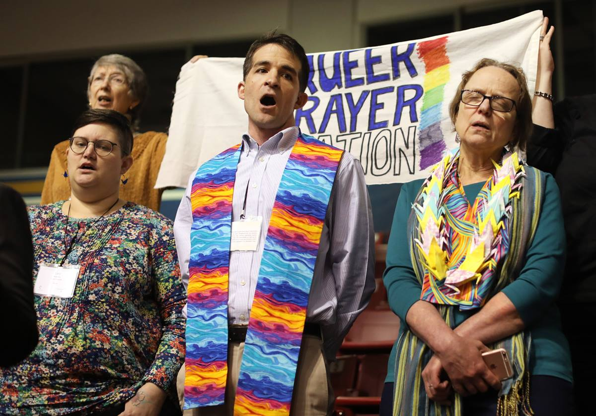 "The Rev. Will Green (center) leads the singing of ""Jesus Remember Me When You Come Into Your Kingdom"" at the ""Queer Prayer Station"" during the Feb. 23 morning of prayer at the 2019 Special Session of the United Methodist General Conference in St. Louis. Green serves one of nine New England churches looking into leaving the denomination. Photo by Kathleen Barry, UMNS."