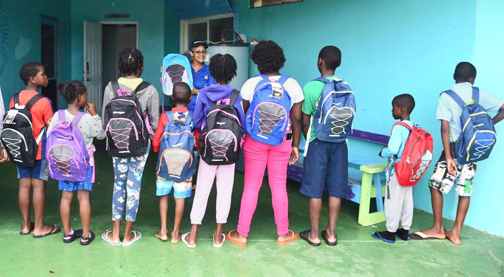 Rotary Club president Susan Culmer presents backpacks to students in a shelter for Hurricane Dorian evacuees at Bahamas Methodist Habitat on Eleuthera Island. The backpacks were donated by the local Rotary Club. Photo by Maisie Thomson.
