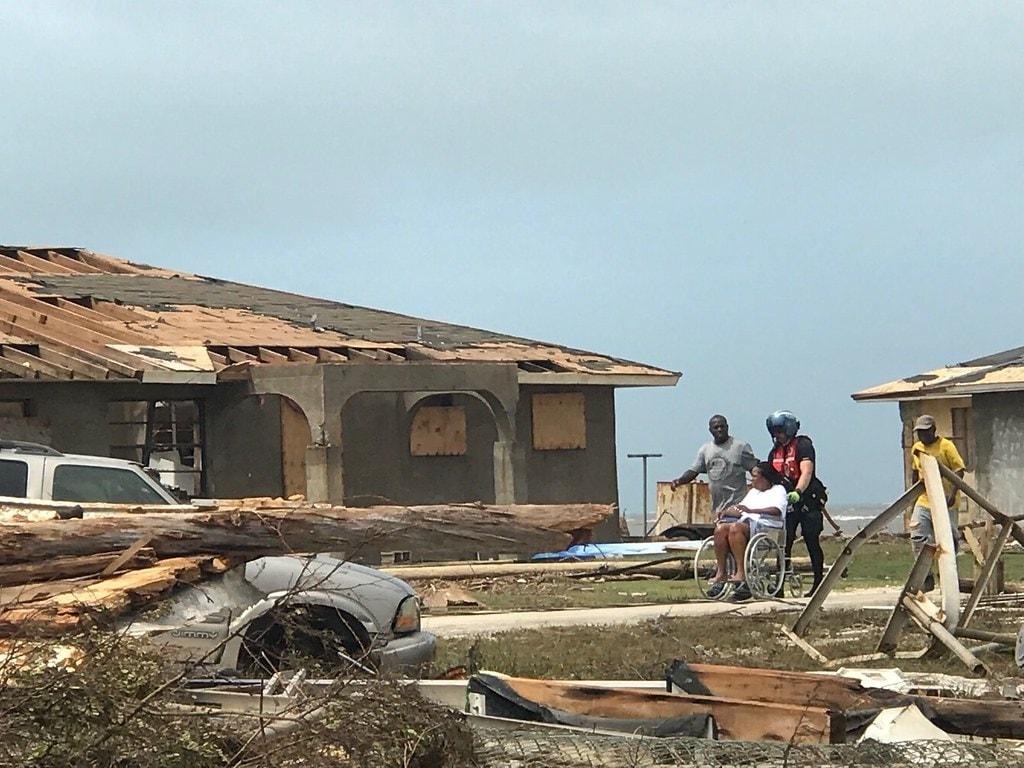 Un miembro de la tripulación del helicóptero de la Guardia Costera MH-60 Jayhawk ayuda a un grupo de personas que necesitan atención médica en las Bahamas, el 4 de septiembre. La Guardia Costera está apoyando a la Agencia Nacional de Manejo de Emergencias de las Bahamas y a la Fuerza Real de Defensa de las Bahamas, quienes lideran los esfuerzos de respuesta, búsqueda y rescate en las Bahamas. Foto por la Guardia Costera de Estados Unidos.