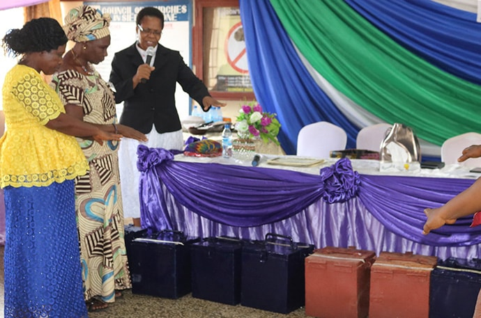 The Rev. Natalia Manyeza blesses loan lock boxes Sept. 6 at the end of a four-day women's empowerment training in Freetown, Sierra Leone. Photo by Phileas Jusu, UM News.