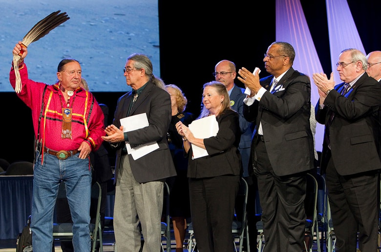 """The Rev. George Tinker (left) receives the applause of United Methodist Church leaders after giving the sermon during an """"Act of Repentance Toward Healing Relationships with Indigenous Peoples"""" at the 2012 United Methodist General Conference. Applauding Tinker (from left, front row) are the Rev. Thom White Wolf Fassett and bishops Mary Ann Swenson, Robert E. Hayes Jr. and Larry M. Goodpaster. Mike DuBose, UM News."""