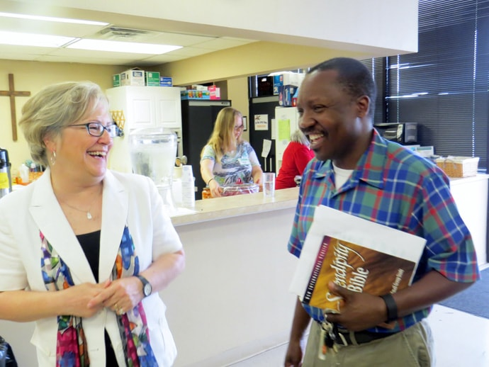 The Rev. Pam Clark, a full-time local pastor who leads community ministries at Dallas' Lake Highlands United Methodist Church, chats with Edgar Moyo. They're at New Room Community Church, a storefront ministry of Lake Highlands. Photo by Sam Hodges, UMNS.