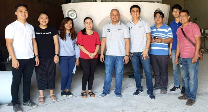 Ryan John de Lara (center), a member of United Methodist City Temple in Cabanatuan City, poses with other researchers in front of the rescue vehicle he helped create. He serves as director of engineering research and productivity at Wesleyan University-Philippines. Photo courtesy of Ryan de Lara.