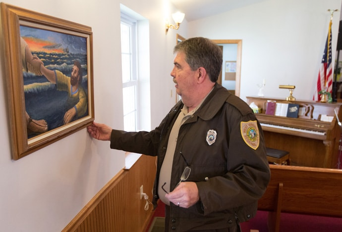 The Rev. Bradley Barton straightens a painting at Union Chapel United Methodist Church in St. George, W.Va. Barton is a correctional officer at the Tygart Valley Regional Jail in Belington and a licensed local pastor in The United Methodist Church. Photo by Mike DuBose, UMNS.