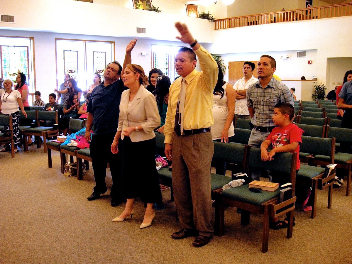 Lay missioner Ruben Rivera (hand raised in worship) prays with his wife, Julissa, at the La Luz de Cristo at Epworth United Methodist Church in Elgin, Ill. UMNS photo by J. Martin Lee.