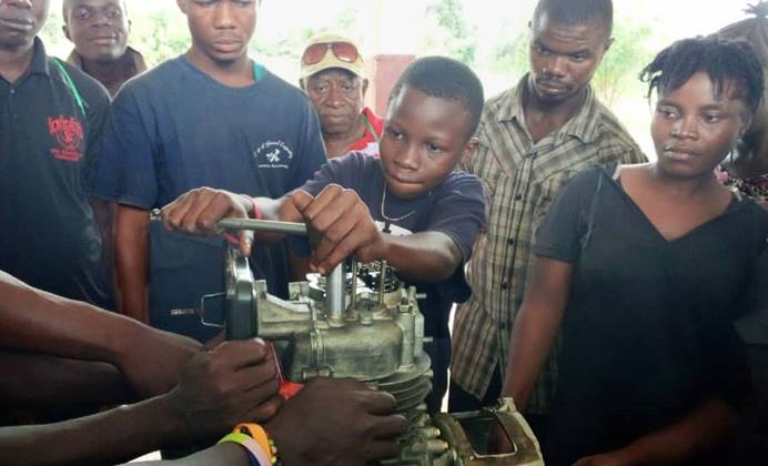 Peter Alfred Jusu, 15, works on a generator engine during hands-on training at the new Taiama Enterprise Academy in Taiama, Sierra Leone, on Oct. 15. Envisioned four years ago, the school is a hybrid of hands-on vocational and entrepreneurship training designed to address the problems of unemployment and poverty. Photo by Duramani Massavoi, Taiama Enterprise Academy.