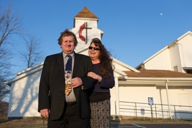 The Rev. Jamie Sprague and his wife, Kay, stand in front of Kanawha Chapel United Methodist Church in Davisville, W.Va., where Sprague serves as a licensed local pastor. Photo by Mike DuBose, UM News.