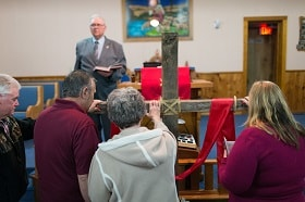 The Rev. Earl Bible invites parishioners to the cross during the Good Friday service at Whitmer United Methodist Church in Seneca Rocks, W.Va. Photo by Mike DuBose, UM News.