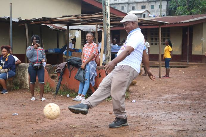 The Rev. Julius Sarwolo Nelson kicks the ball during a soccer match between youth and young adults in Monrovia, Liberia.  A scholarship fund to help young people in rural communities has been named after Nelson, who is an elder at Refuge United Methodist Church. Photo by E Julu Swen, UM News.