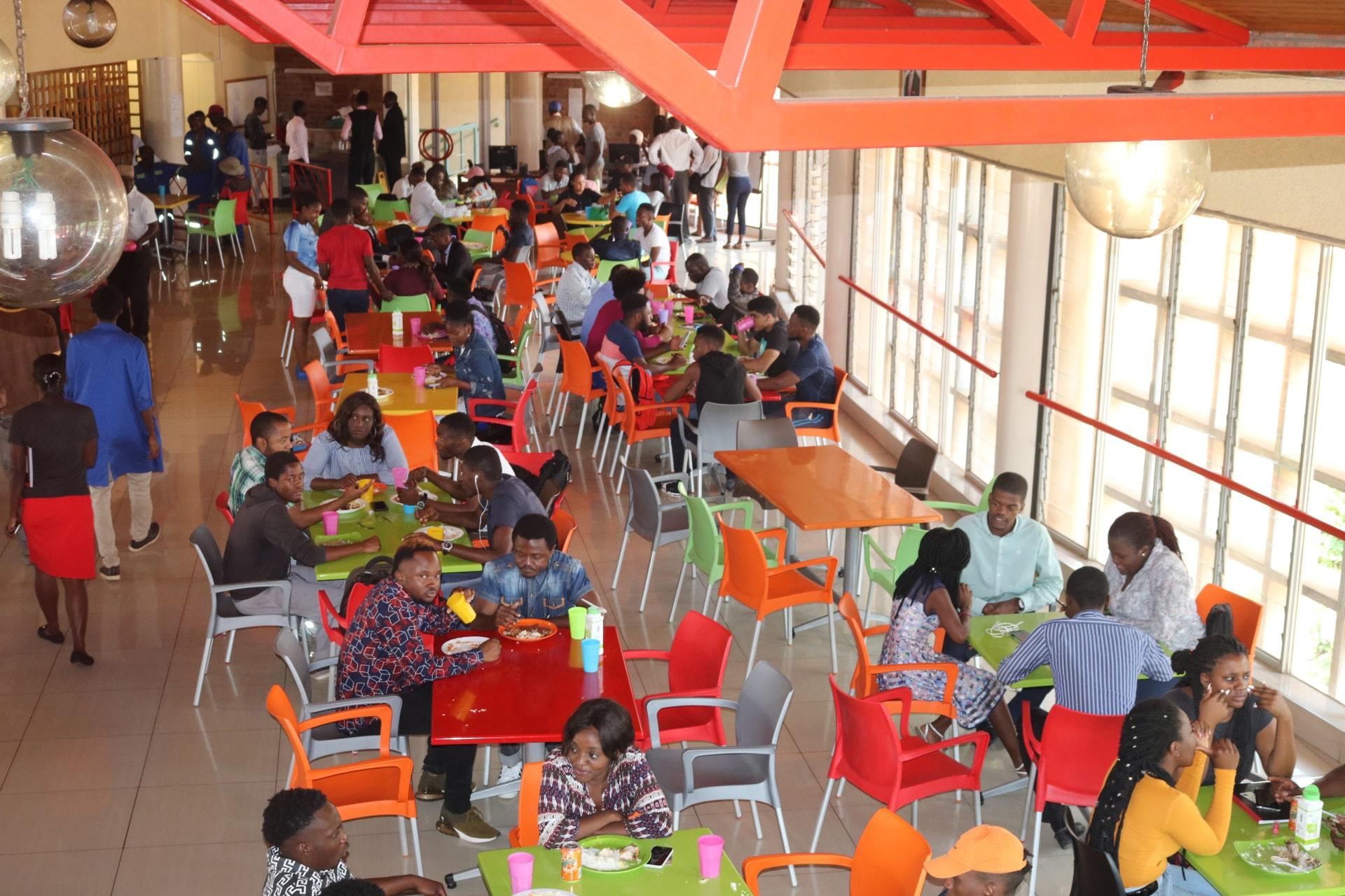 Los/as estudiantes comen en la cafetería de la Universidad de África, que sirve a unas 1.200 personas durante el almuerzo y la cena. Para manejarse en tiempos económicos difíciles, el departamento de servicios de alimentos ha estado suministrando alimentos y administrando porciones. Foto por Eveline Chikwanah, Noticias MU.