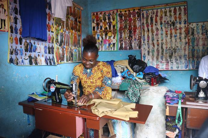 Marian Sao Ensah, a new graduate of the Bo Women's Training Center, works with a team of tailors at Old Railway Line in Bo, Sierra Leone. Ensah, a single mother of four, said the skills training she received has made it easier for her to provide for her children. Photo by Phileas Jusu, UM News.