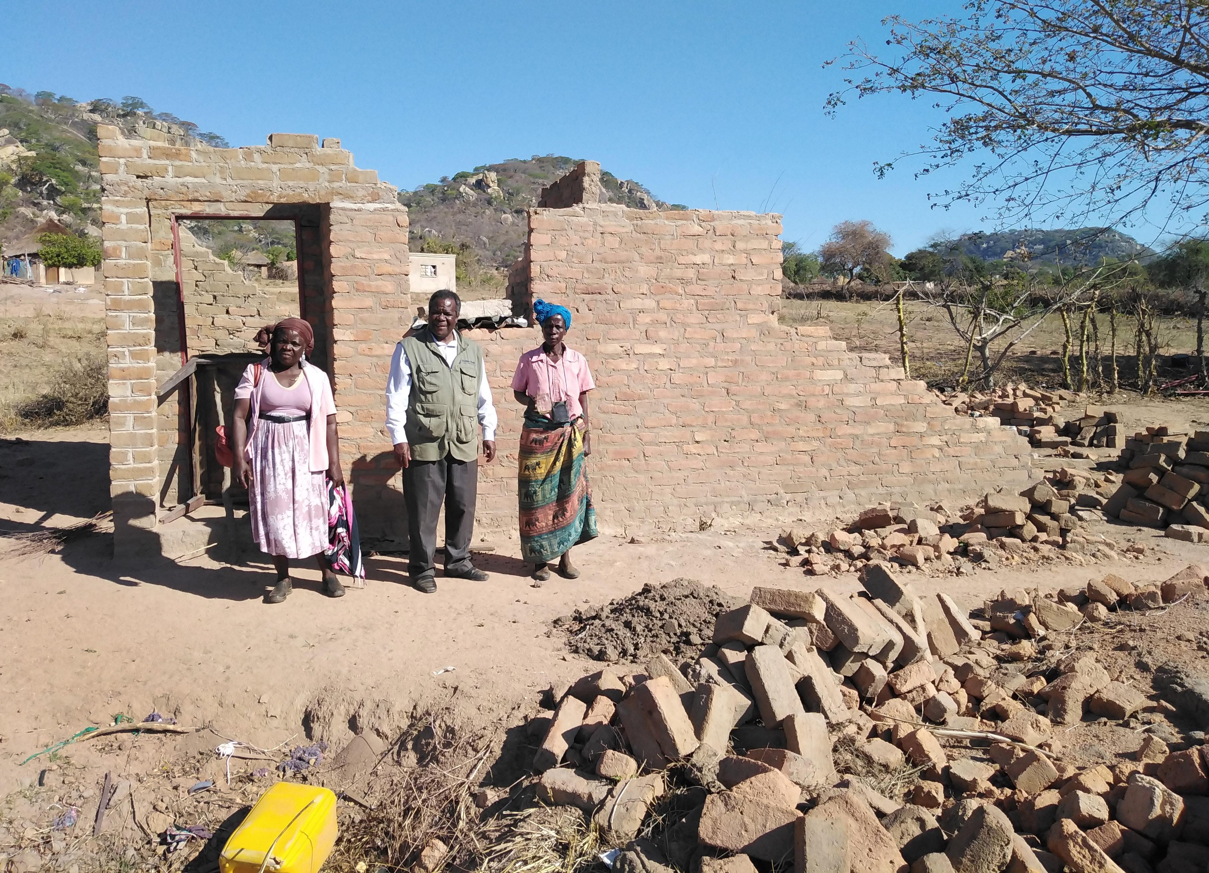 Vivian Chigweshe, à droite, se tient devant sa maison, qui a été détruite par le cyclone Idai en mars. Elle est l'une des survivants qui grâce au soutien de l'Église Méthodiste Unie se feront construire une nouvelle maison. (A partir de la gauche sur la photo), le leader laïc Chirobwe Kupeti et le révérend Jairos Mafondokoto, surintendant du district de Masvingo. Photo de Chenayi Kumuterera, UM News.