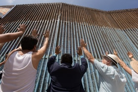 The Revs. Joel Hortiales (center, in blue blazer) and David Farley (to Hortiales' right) join parishioners of the Border Church in Tijuana, Mexico, as they lift their arms skyward beneath the fence that marks the border with the U.S. Photo by Mike DuBose, UM News.