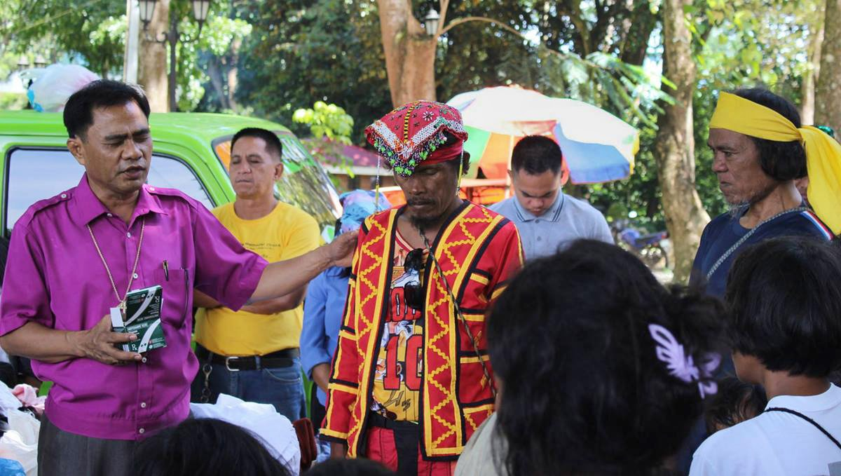 Bishop Rodolfo A. Juan (left) prays for a leader (red vest) at a camp for displaced people in Malaybalay, Philippines, in 2017. The United Methodist Church in the Philippines has condemned extrajudicial killings and other human rights abuses in the country, as well as protesting the treatment of indigenous people. The church has worked both alone and through ecumenical groups like the National Council of Churches. File photo courtesy of Dan Ela.