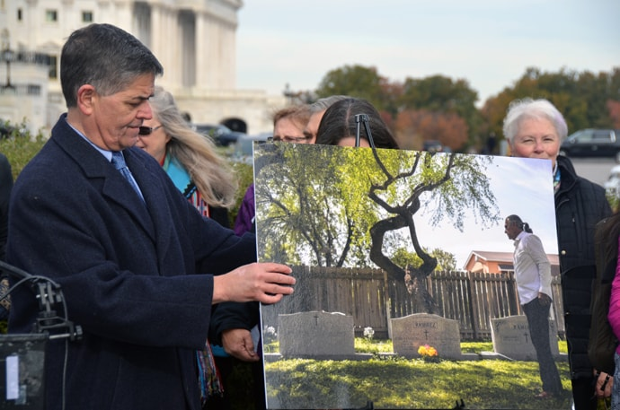 U.S. Rep. Filemon Vela, a Texas Democrat, adjusts a photo of Jackson Chapel United Methodist Church's historic cemetery in San Juan, Texas, during a press conference protesting President Trump's proposed border wall. Photo by Erik Alsgaard, UM News.