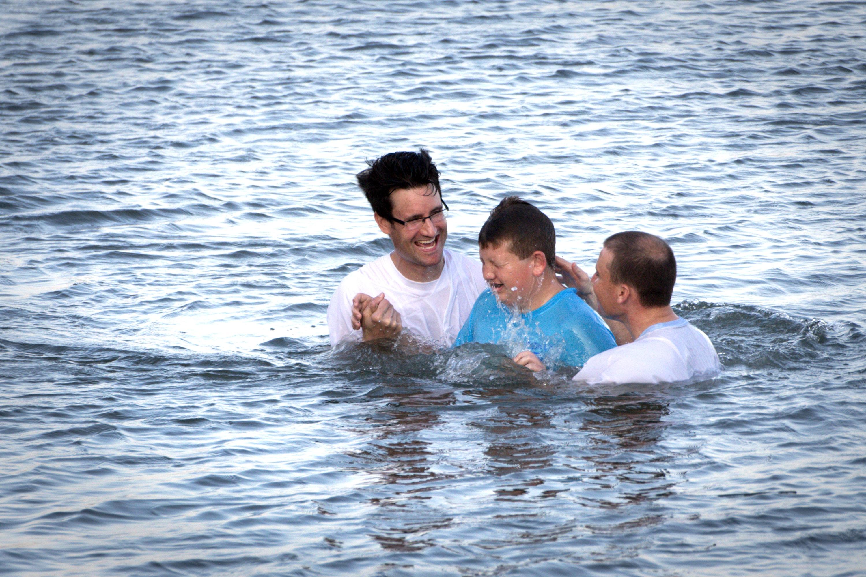 Marshall Greene (centro) é batizado durante o Batismo Anual de Admissão em Murrells Inlet, próximo ao paredão da Igreja Metodista Unida Memorial Belin. Segurando-o (à esquerda) Austin Bond, diretor de ministérios da juventude e (à direita) Walter Cantwell, pastor associado. Foto de Benjamin Coy.