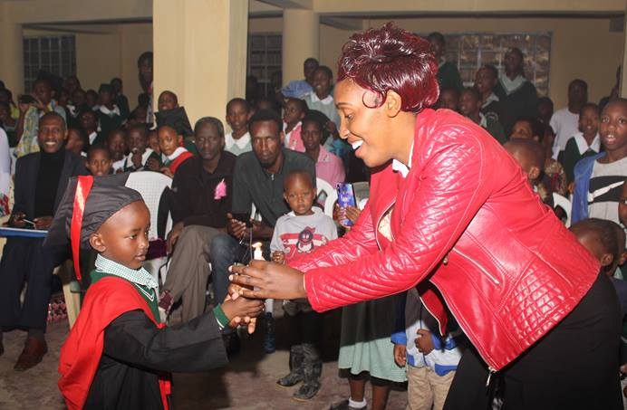 A Congolese student passes on a candle to his teacher as a symbol of successfully completing the Early Years of Education course at Dr. B.T. Cooper United Methodist School in Nairobi, Kenya. Of the 310 students enrolled at the school, 200 are Congolese children with refugee status. Photo by Gad Maiga, UM News.