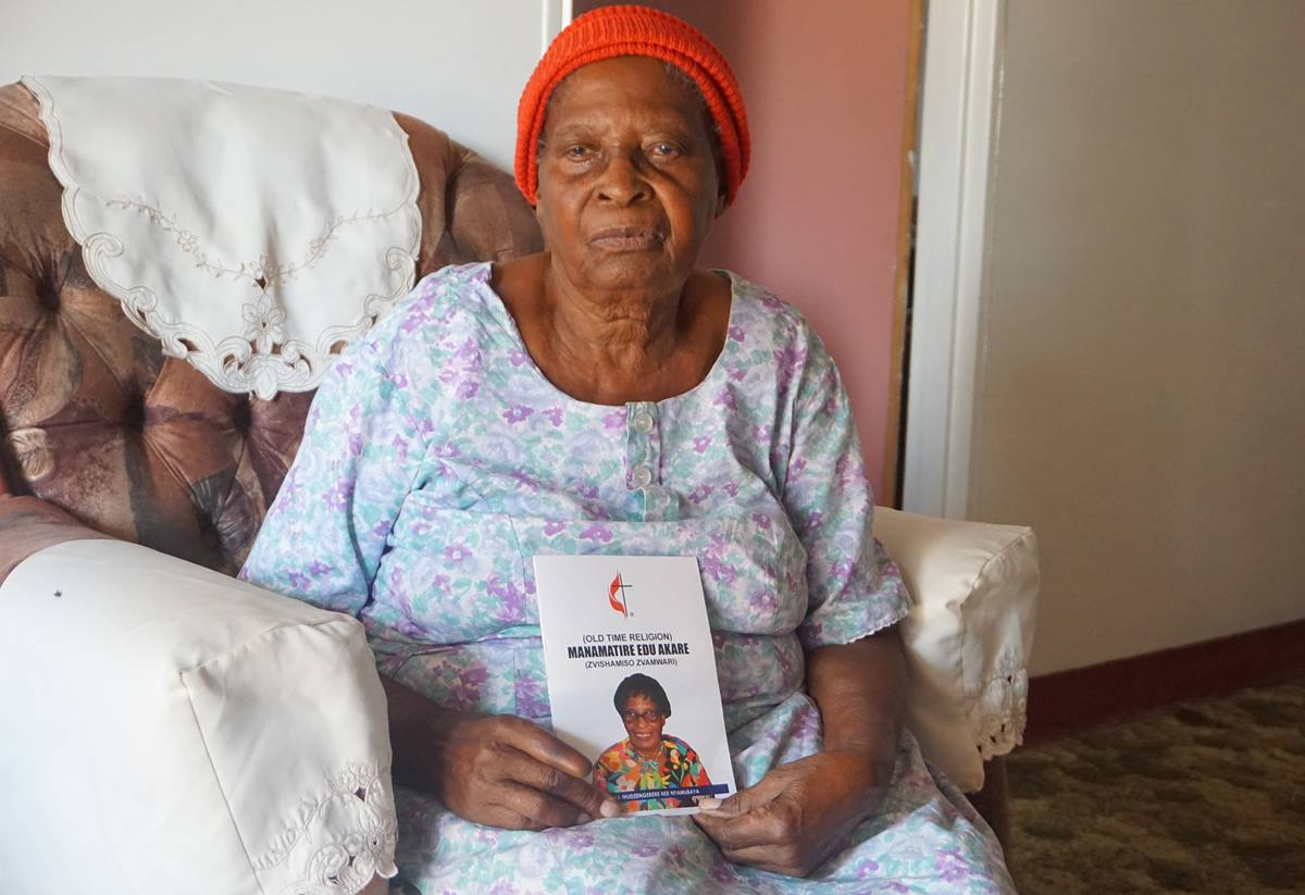"Martha ""Granny"" Mudzengerere shows off her new book, ""Old Time Religion,"" which includes spiritual guidance and history about The United Methodist Church in Zimbabwe. It is the 104-year-old's first book. Photo by Kudzai Chingwe, UM News."