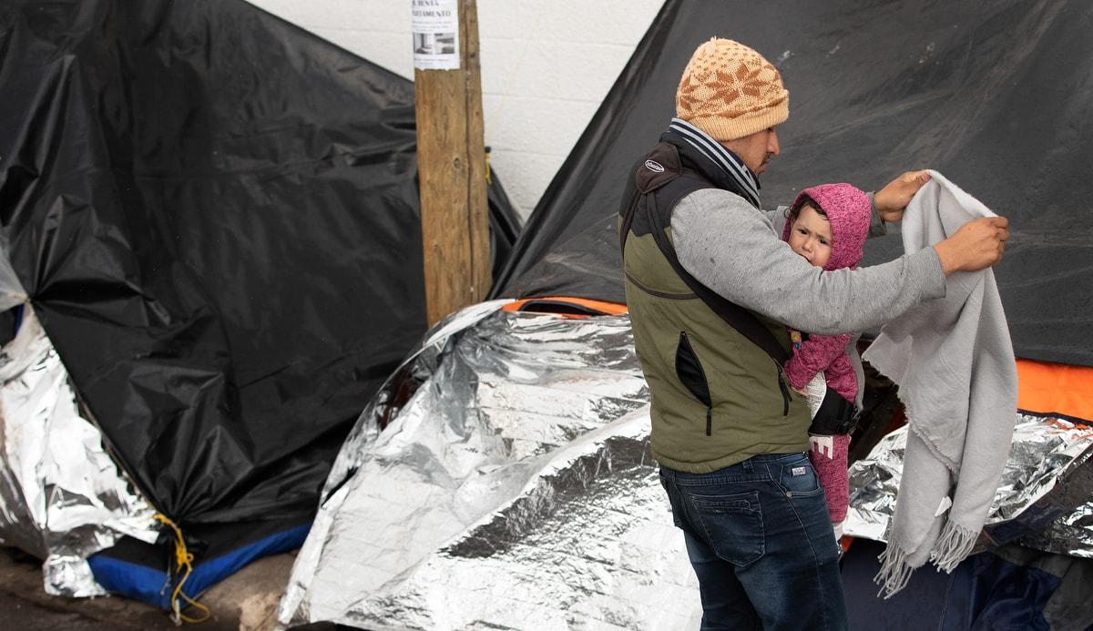 """Jesús, um migrante do estado de Michoacán, no oeste do México, tenta proteger sua filha Kataleya, de um ano de idade, de uma garoa fria que cai no acampamento onde moram aos pés da ponte Paso del Norte, em Juárez, México. Michoacán está entre os cinco estados do México, com o aviso de maior risco de """"não viajar"""" do Departamento de Estado dos EUA."""