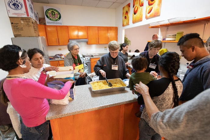 Volunteers from El Calvario United Methodist Church in Las Cruces, N.M., serve a meal for migrants at an immigrant processing center in Juárez, Mexico, at the foot of the Paso del Norte border crossing into El Paso, Texas. Volunteers from Mexico and the U.S. serve regular meals and offer educational programming for children while families wait to make asylum claims in the U.S. Photo by Mike DuBose, UM News.