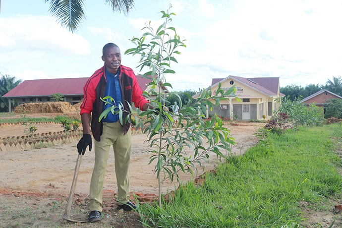 The Rev. Felix Okende maintains a tree he planted in front of Kitumaini United Methodist Church in in the South Kindu District of East Congo, where he is pastor. The agronomist plants trees next to United Methodist churches, schools and health centers to help protect the environment. Photo by Chadrack Londe, UM News.