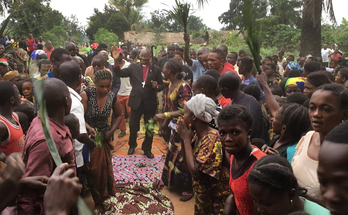 People in the village of Samba, Congo, line the streets to welcome East Congo Bishop Gabriel Yemba Unda, who spent 10 days in late September and early October visiting all seven districts in the remote East Congo Conference. It was the first time many United Methodists in the area had ever seen a bishop. Photo by Judith Osongo Yanga, UM News.