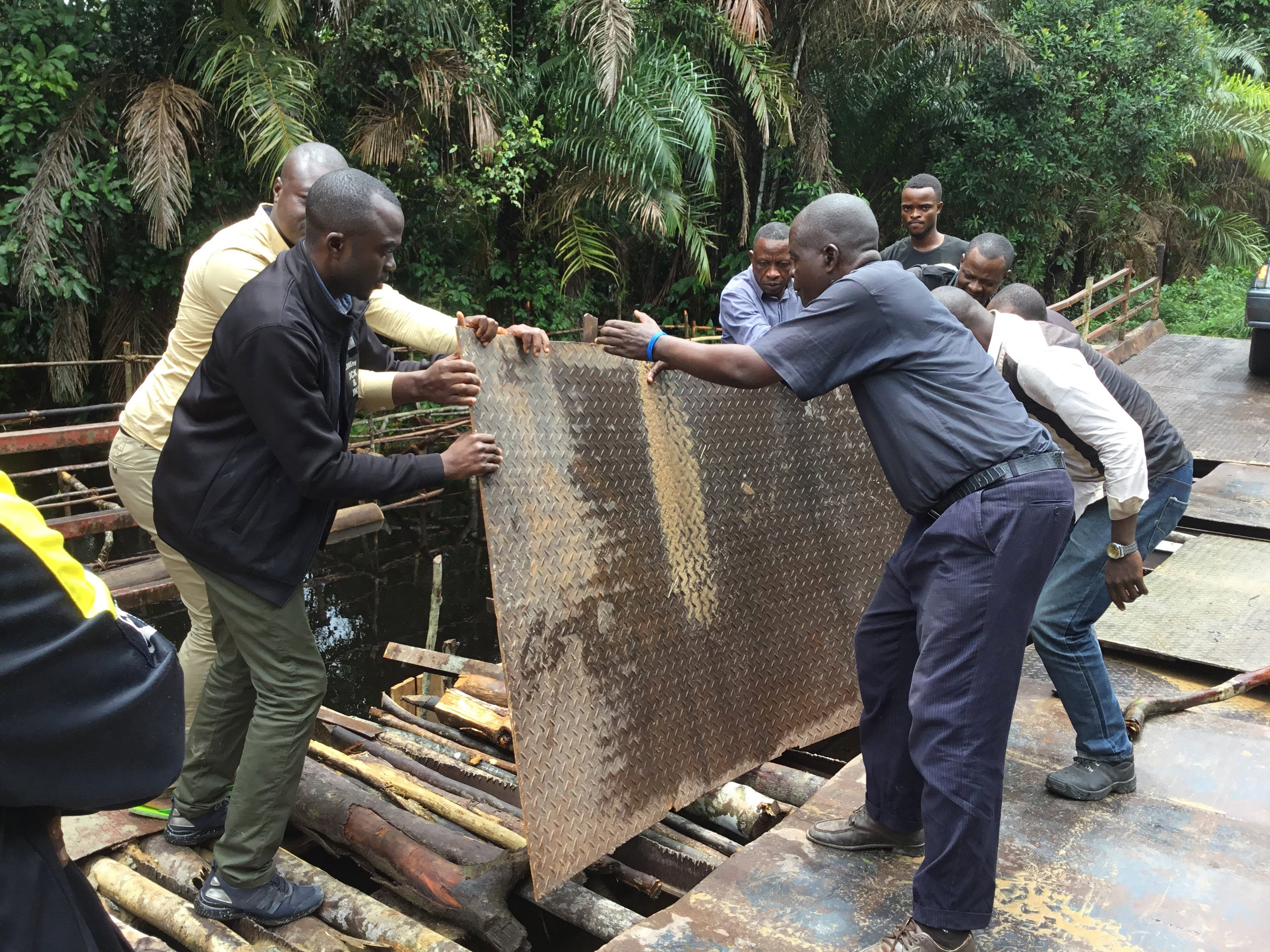 Men lay a metal sheet over a broken bridge so that Bishop Gabriel Yemba Unda and his delegation can continue their travels to some of the most remote areas in the East Congo Conference. Photo by Judith Osongo Yanga, UM News.