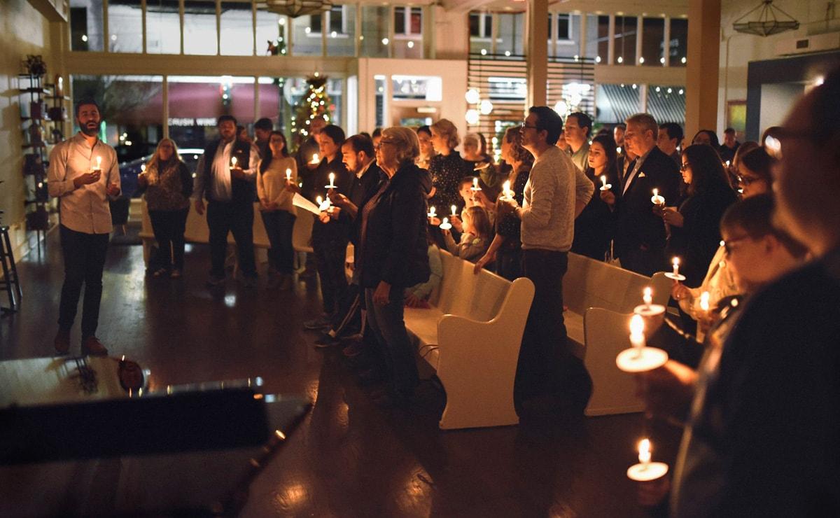 """El Rev. Will Choate, a la izquierda, ayuda a los fieles a cantar """"Noche de Paz"""" a la luz de las velas en la víspera de la Navidad de 2018 en la Iglesia Metodista Unida (IMU) Argenta en North Little Rock, Arkansas. La creciente congregación y otros/as en toda la conexión metodista unida se están preparando para hacer que los/as visitantes se sientan bienvenidos/as. Foto cortesía de la IMU Argenta."""