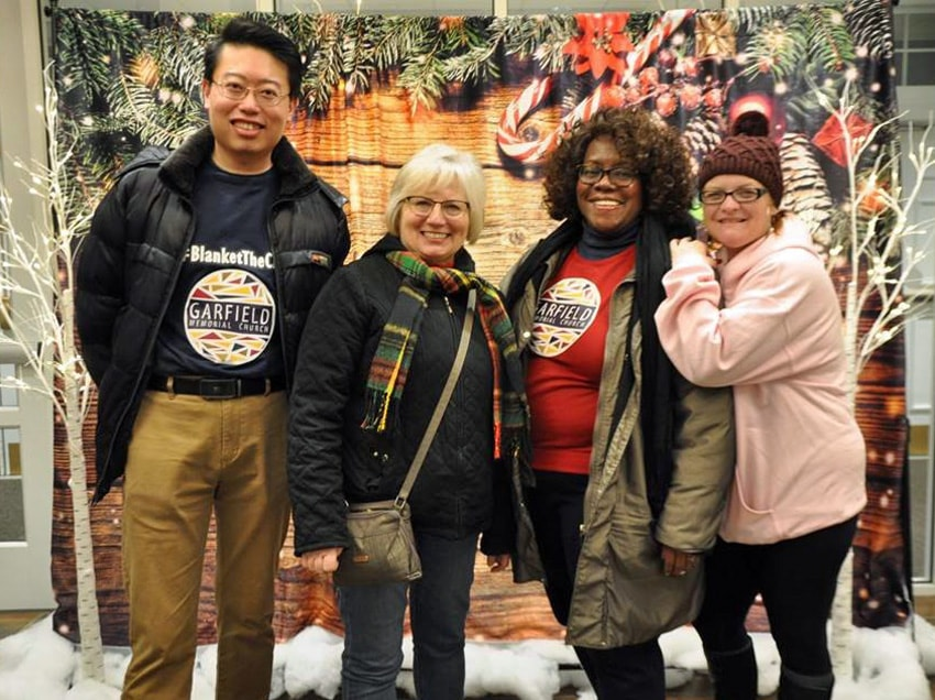 Garfield Memorial Church near Cleveland, Ohio, finds various ways to be make people feel welcome, including having a backdrop where people can take Christmas photos. From left are David Chung, Cheri Shumaker, Johnnie Hilliard and Nikki Froehlich. Photo courtesy of Garfield Memorial Church.