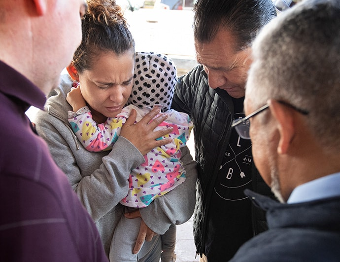 The Rev. Arturo Gonzélez Sandouzl (second from right) and other members of the United Methodist Immigration Task Force pray with Isabél and her 16-month-old daughter Kassandra at a makeshift camp near the bridge leading to the U.S. in Matamoros, Mexico. The mother and daughter traveled from Nicaragua in hopes of seeking asylum in the U.S. Photo by Mike DuBose, UM News.