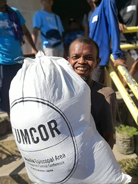 An earthquake survivor in the Nabuklod community in Floridablanca, Philippines, shares a smile after receiving food distributed by The United Methodist Church in the Philippines and funded by the United Methodist Committee on Relief. Photo by the Rev. Gilbert Cedillo.