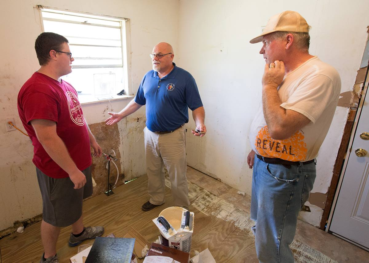 Dale Kimball (center) checks in with Nicholas Eldred (left) and Jerry Rouse on the progress of repairs to a home damaged by Hurricane Katrina in Slidell, La. The Epworth Project, which hosts volunteers from across the country, has a full slate of recovery projects underway 10 years after Hurricane Katrina. Kimball is executive director and Eldred is on staff at the Epworth Project. Rouse is helping lead a youth teach from Wichita Falls (Texas) First United Methodist Church. Photo by Mike DuBose, UMNS.