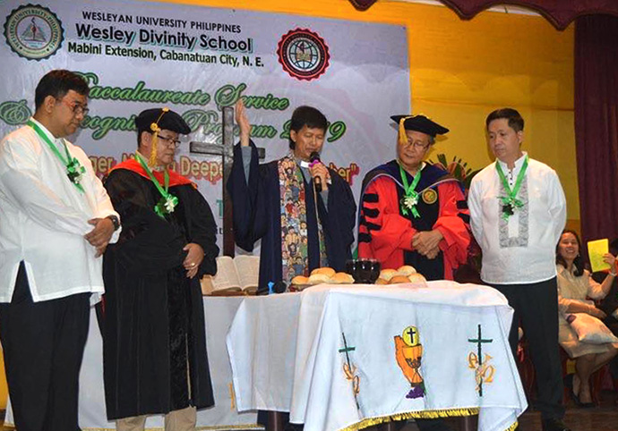 Bishop Pedro M. Torrio Jr. (center) officiates Holy Communion during the Jan. 25, 2019, Baccalaureate service at Wesley Divinity School of Wesleyan University in Cabanatuan City, Philippines. From left are the Rev. Francis Fajardo, the Rev. Sergio E. Arevalo Jr., Torio, Johnson Mones and Willy Ramos. Photo courtesy of the Rev. Sergio E. Arevalo Jr.
