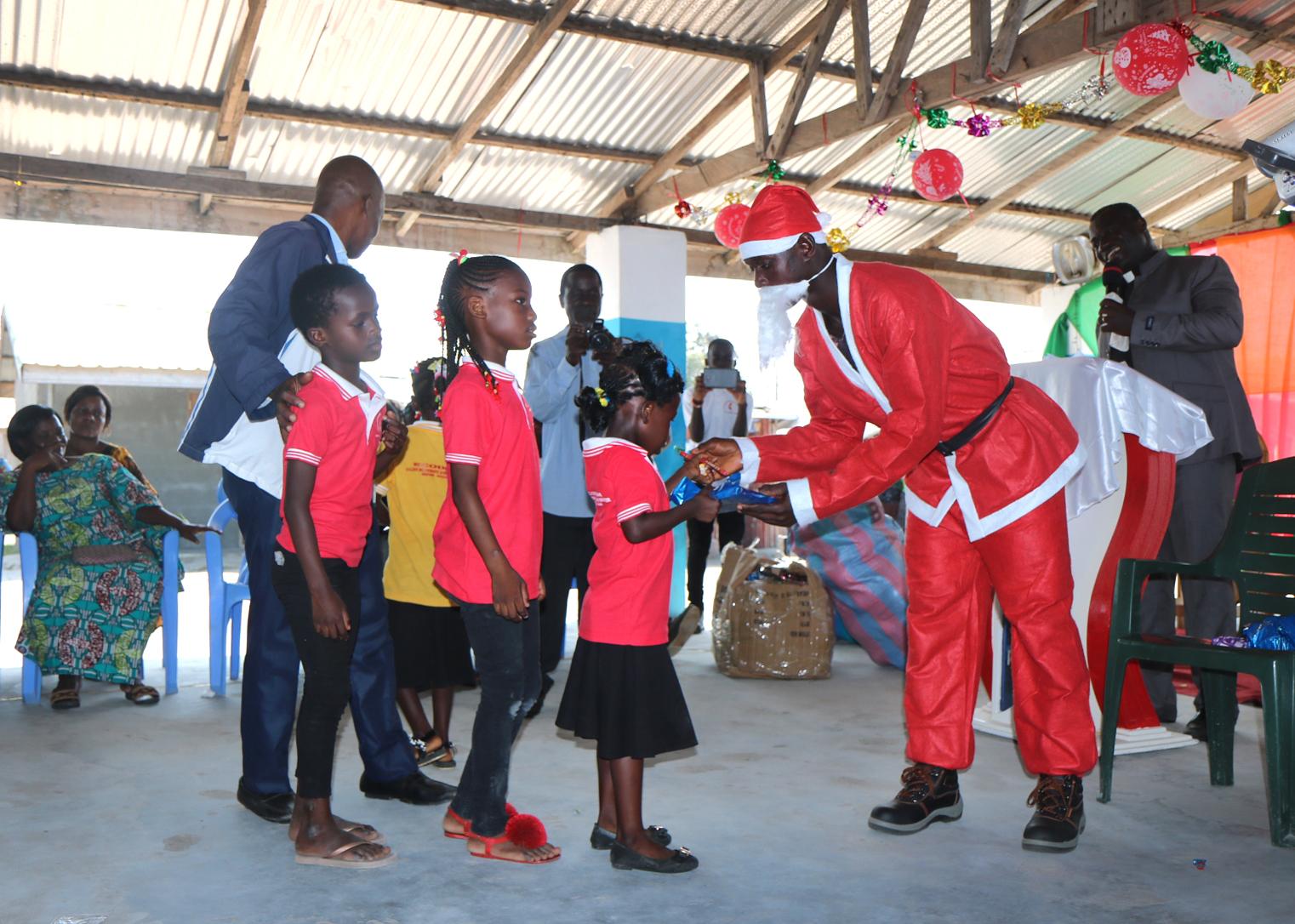 Les enfants ont fait la queue pour recevoir un cadeau du Père Noël au camp de réfugiés Ivoiriens d'Ampain le jour de Noël. Le district d'Aboisso de l'Église Méthodiste Unie de Côte d'Ivoire a organisé la célébration et la distribution de cadeaux pour plus de 540 enfants. Photo de Isaac Broune, UM News.