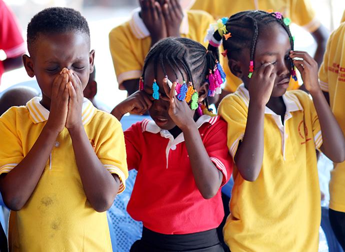 (A partir de la gauche) Eunice Mel, 9 ans, Syntiche Tia, 5 ans, et Gnonsio Tryphene, 9 ans, membres de l'église Méthodiste Unie Bethel du camp de réfugiés Ivoriens d'Ampain (Ghana) prient durant une célébration d'arbre de Noël organisé dans le camp. Le district d'Aboisso de l'Église Méthodiste Uie de Côte d'Ivoire soutient cette communauté. Photo de Isaac Broune, UM News.