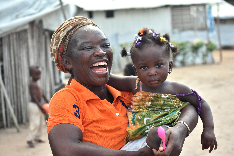 Josiane Bahi, 33 ans, tient dans ses bras sa petite-fille Grâce Debra de 1 an, dans le camp de réfugiés ivoiriens d'Ampain (Ghana), où Josiane Bahi, une Méthodiste Unie, réside depuis 2012. Sa petite-fille faisait partie des plus de 540 enfants qui ont reçu un présent de l'Église Méthodiste Unie de Côte d'Ivoire le jour de Noël. Photo de Isaac Broune, UM News.