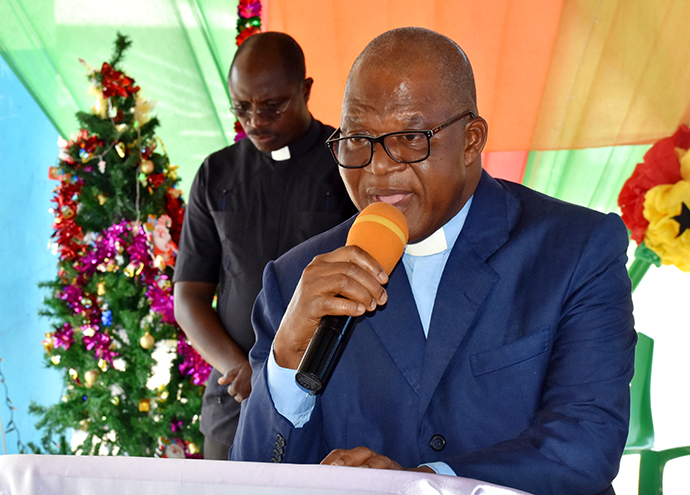 The Rev. Alphonse Affi, Aboisso District superintendent for The United Methodist Church in Côte d'Ivoire, speaks to children at Ampain Ivorian Refugee Camp in Ampain, Ghana. The church organized a Christmas Day celebration for more than 540 children at the camp. In the background is the Rev. Mensah Goka Kodjo, chaplain of Methodist University of Côte d'Ivoire. Photo by Isaac Broune, UM News.