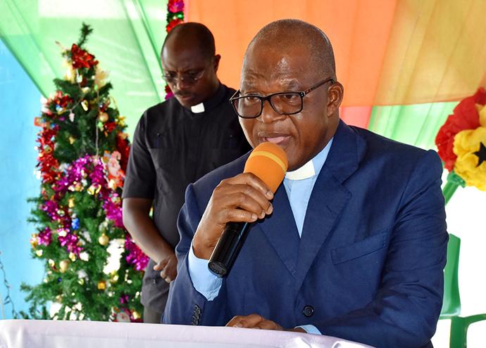 Le Révérend Alphonse Affi, Surintendant du District d'Aboisso de l'Eglise Méthodiste Unie-Côte d'Ivoire, s'adresse aux enfants du camp des réfugiés Ivoiriens d'Ampain (Ghana). L'église a organisé un arbre de Noël pour plus de 540 enfants dans ce camp. En arrière-plan, le Révérend Mensah Goka Kodjo, Aumônier de l'Université Méthodiste de Côte d'Ivoire. Photo de Isaac Broune, UM News.