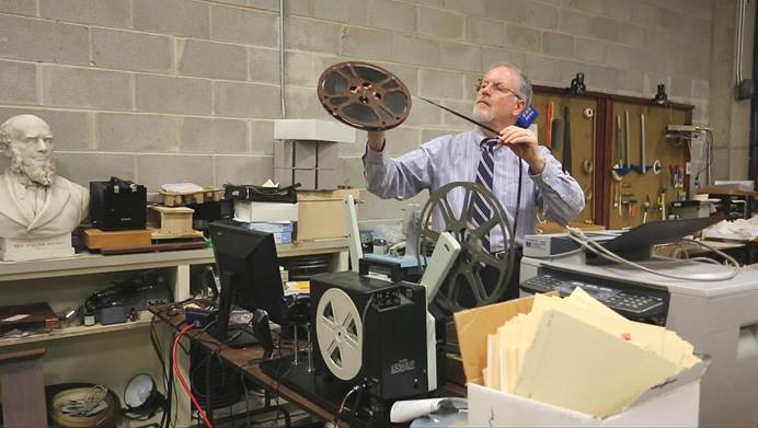 L. Dale Patterson, archivist-records administrator at the United Methodist Commission on Archives and History, examines film, one of thousands of carefully filed items at the agency housed on the campus of Drew University in Madison, New Jersey. A 2013 file photo by Kathleen Barry, UM News.