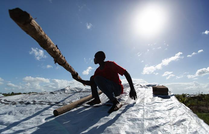 Jorge João Novo lifts a wooden pole into place to help secure an emergency tarp over his home after the roof was peeled off by Cyclone Idai in Buzi, Mozambique. Photo by Mike DuBose, UM News.