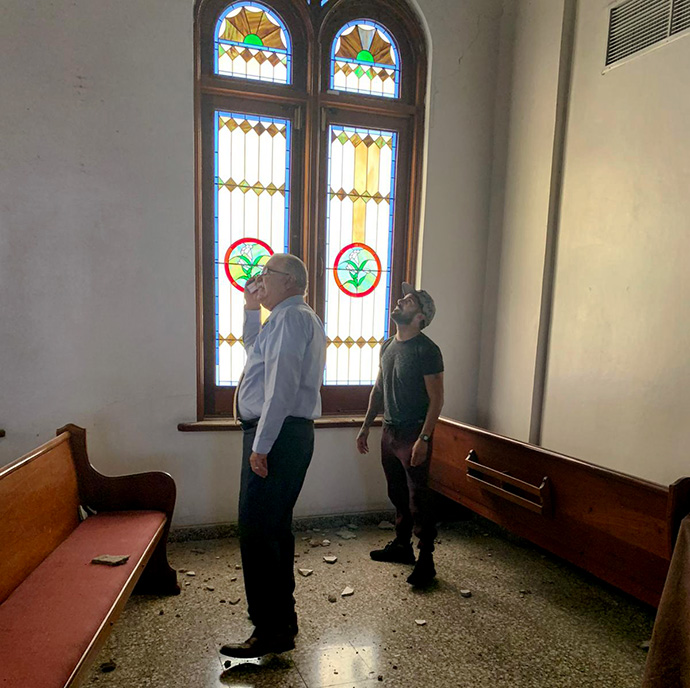 Bishop Hector F. Ortiz (left) of the Methodist Church of Puerto Rico surveys earthquake damage at the Church of the Resurrection in Ponce. The stained-glass windows behind him, previously damaged by Hurricane Maria, were repaired with hurricane recovery funds. Photo courtesy of the Methodist Church of Puerto Rico.