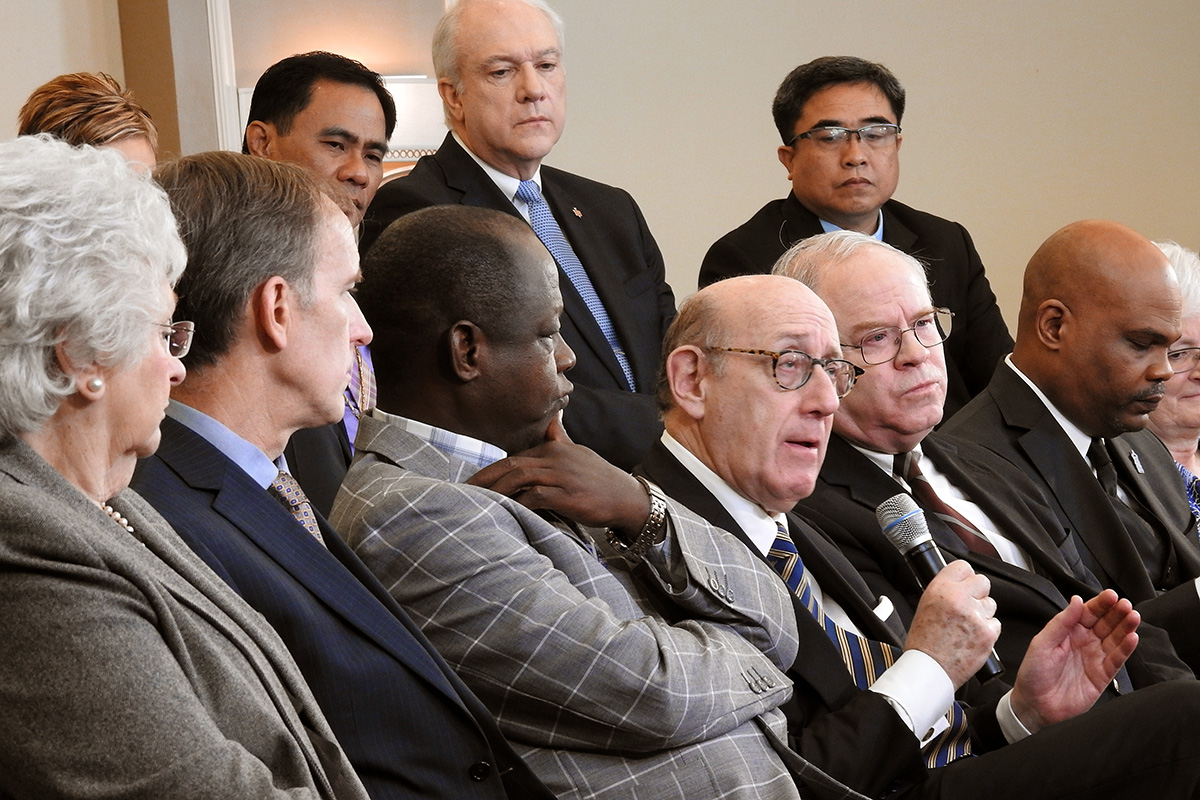 """Kenneth Feinberg (holding microphone), speaks during a livestreamed panel discussion in Tampa, Fla., with members of the team that developed a new proposal that would maintain The United Methodist Church but allow traditionalist congregations to separate into a new denomination. Feinberg moderated the work of the team that created the proposal, called the """"Protocol of Reconciliation & Grace Through Separation."""" Photo by Sam Hodges, UM News."""