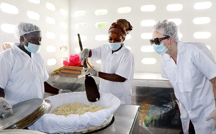 Lorrie King (right), director of Sustainable Development for the United Methodist Committee on Relief, watches as Akossi Lobochi Rosine (left) and Ayibé Carine make attiéké at a new processing plant in Anyama, Côte d'Ivoire. Attiéké is an Ivorian dish made from cassava flour that is similar in texture to couscous. Photo by Isaac Broune, UM News.