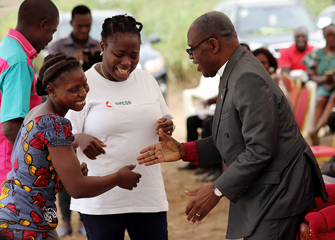 Bishop Benjamin Boni, Côte d'Ivoire Episcopal Area (right), congratulates Angèle Seri, deputy president of United Methodist Women in Issia, during the Jan. 11 inauguration of an attiéké processing plant in Anyama, Côte d'Ivoire. In the middle is Gisèle Koké, project coordinator for le Réservoir de Siloé, the United Methodist organization that built the plant. Photo by Isaac Broune, UM News.